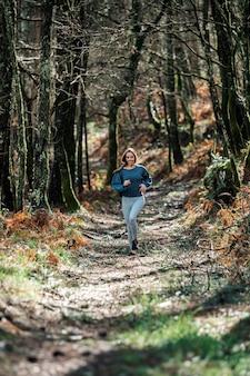 Dopasowana kobieta w odzieży sportowej biegnącej szlakiem w zielonym lesie