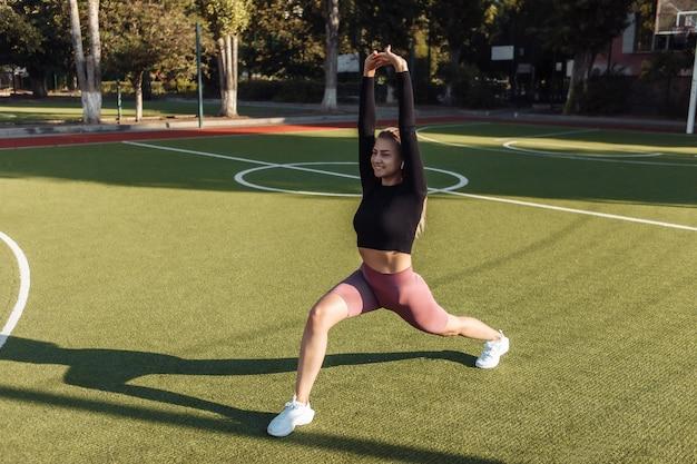 Dopasowana kobieta w sportowej rozgrzewce przed treningiem, rozciąganie ciała na stadionie. pojęcie zdrowego stylu życia. trening na zewnątrz