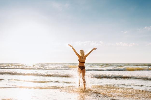 Dopasowana kobieta yound spacerująca wzdłuż linii morskich fal i podnosząca spray i morską pianę. wakacje, wakacje. strzelaj od tyłu.