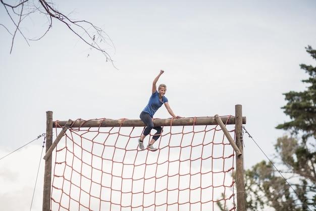 Dopasowana kobieta z ręką uniesioną do góry świętuje sukces podczas toru przeszkód w obozie treningowym