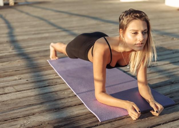 Dopasowana młoda wysportowana kobieta robi ćwiczenie deskowania pracujące nad mięśniami brzucha na świeżym powietrzu o poranku