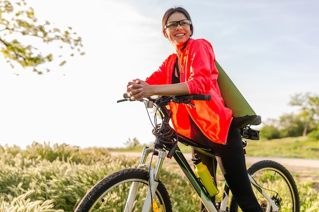Dopasowana piękna kobieta uprawia sport rano w parku, jazda na rowerze z matą do jogi w kolorowym stroju fitness, odkrywanie natury, uśmiechanie się szczęśliwy zdrowy styl życia