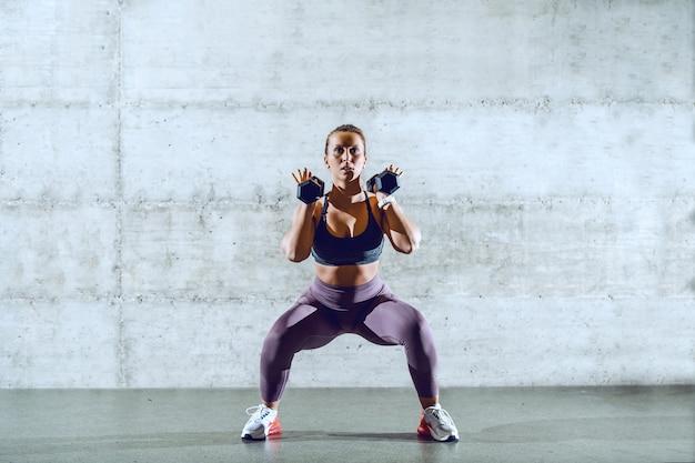 Dopasowana sportowa brunetka w odzieży sportowej z kucykiem robi przysiady trzymając hantle