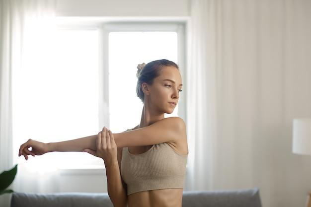 Dopasowana sportowa kobieta ćwicząca i trenująca w domu