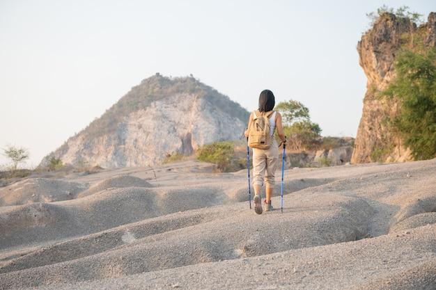 Dopasowana turystka z plecakiem i kijkami stojąca na skalistym grzbiecie górskim z widokiem na doliny i szczyty.