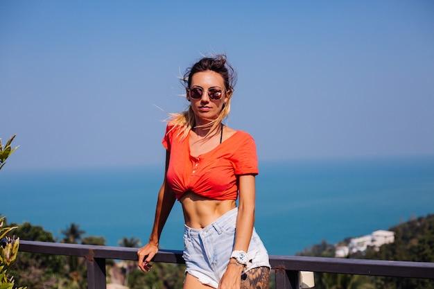 Dopasowana, wysportowana, wytatuowana kaukaska europejka o sportowej sylwetce i mięśniach brzucha, w dżinsowych szortach i czerwono-pomarańczowej koszuli