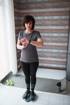 Dopasowanie dorosłej szczupłej kobiety ma trening w domu. dojrzały starszy model stoi na wadze i spogląda na inteligentny zegarek. śledź jej wagę. zadbaj o zdrowie w jej wieku.