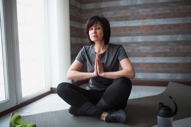 Dopasowanie dorosłej szczupłej kobiety ma trening w domu. poważna skoncentrowana dojrzała kobieta siedzi ze skrzyżowanymi nogami i medytuje. trzymajcie się za ręce i modląc się.