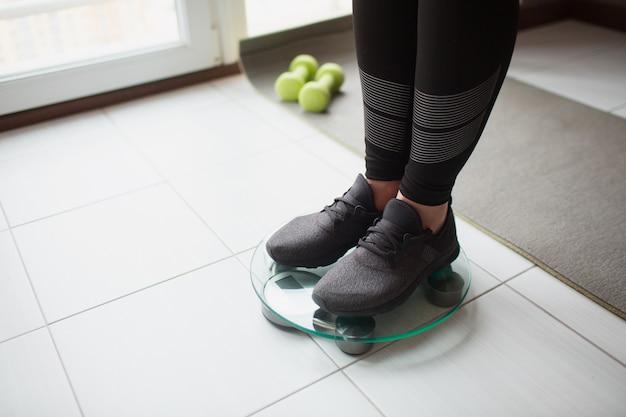Dopasowanie dorosłej szczupłej kobiety ma trening w domu. przekrój nóg w czarnych butach stoi na skali wagi. zadbaj o zdrowie i dobre samopoczucie.