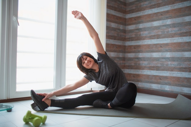 Dopasowanie dorosłej szczupłej kobiety ma trening w domu. starsza dojrzała modelka siedzi z szeroko otwartymi nogami i wyciąga rękę do góry. rozciągając jej całe ciało.