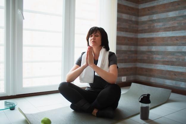 Dopasowanie dorosłej szczupłej kobiety ma trening w domu. starszy model siedzi ze skrzyżowanymi nogami i medytuje lub modli się. rozciągając ręce, trzymając się razem. dbaj o ciało i duszę.
