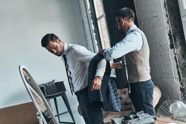 Dopasowanie garnituru. młody modny projektant pomagający swojemu klientowi się ubrać