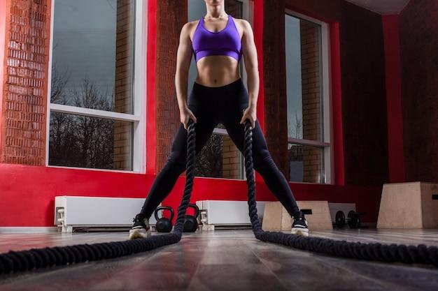 Dopasowanie i muskularna kobieta ćwiczenia z linami walki w fitness