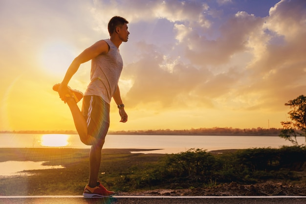 Dopasowanie lekkoatleta mężczyzna robiąc się robi ćwiczenia rozciągające na świeżym powietrzu z zachodem słońca w tle
