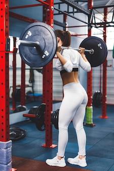 Dopasowanie piękna dziewczyna robi przysiady ze sztangą w siłowni