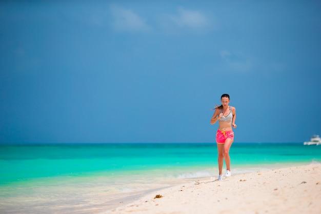 Dopasowanie sportowe młoda kobieta biegnie wzdłuż tropikalnej plaży w swojej odzieży sportowej