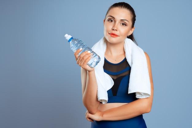 Dopasowanie sportowy kobieta trzyma butelkę wody mineralnej w dłoni
