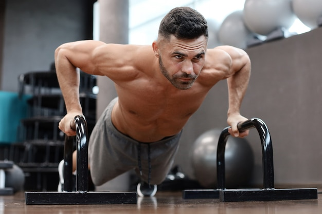 Dopasowany i muskularny mężczyzna robi poziome pompki z paskami w siłowni.