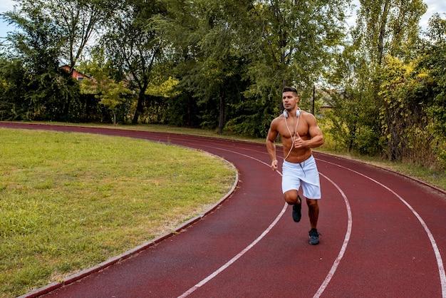 Dopasowany mężczyzna bez koszuli z białymi spodenkami i słuchawkami na szyi, biegający po torze