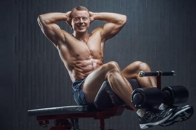 Dopasowany mężczyzna trenujący mięśnie brzucha na ciemnym tle