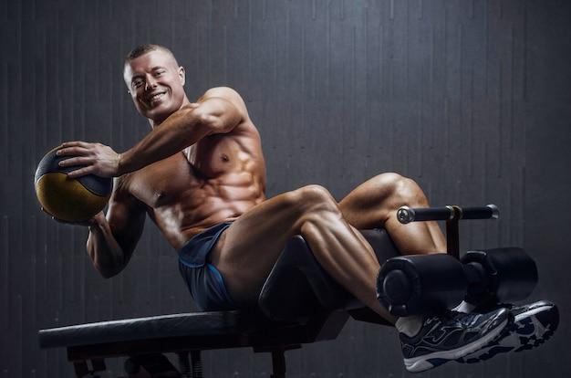 Dopasowany mężczyzna trenujący mięśnie brzucha na siłowni na ciemnym tle