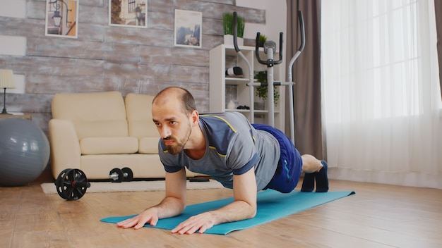 Dopasowany mężczyzna w odzieży sportowej robi trening deski na macie do jogi w domu.