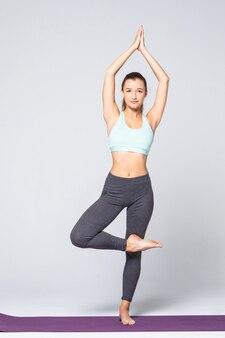 Dopasuj atrakcyjną młodą kobietę uprawiającą jogę o nazwie tree pose, sanskrycka nazwa: vrksasana