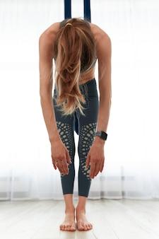 Dopasuj całkiem młoda kobieta robi ćwiczenia rozciągające jogi mucha w sali fitness szkolenia na poddaszu biały siłownia.