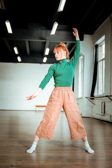 Dopasuj ciało. przyjemnie wyglądająca instruktorka jogi fit w zielonym golfie, skoncentrowana podczas stania w asanie