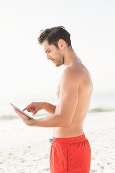 Dopasuj człowieka za pomocą tabletu na plaży