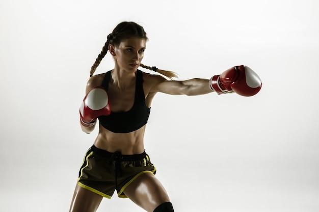 Dopasuj kaukaski kobieta w boksie odzieży sportowej na białym tle na białej ścianie. początkujący bokserka kaukaska kobieta trenuje i ćwiczy w ruchu i akcji. sport, zdrowy styl życia, koncepcja ruchu.
