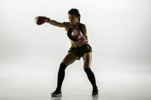 Dopasuj kaukaski kobieta w boksie sportowym na białym tle na białej ścianie. początkująca bokserka kaukaska trenująca i ćwicząca w ruchu i akcji. sport, zdrowy styl życia, koncepcja ruchu.