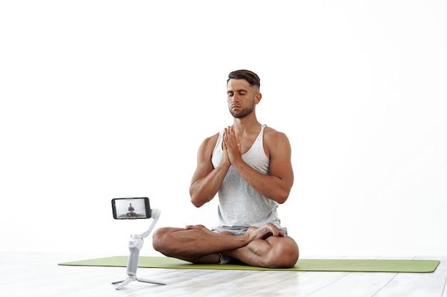 Dopasuj kaukaski mężczyzna nagrywający bloga lub przesyłający strumieniowo trening jogi