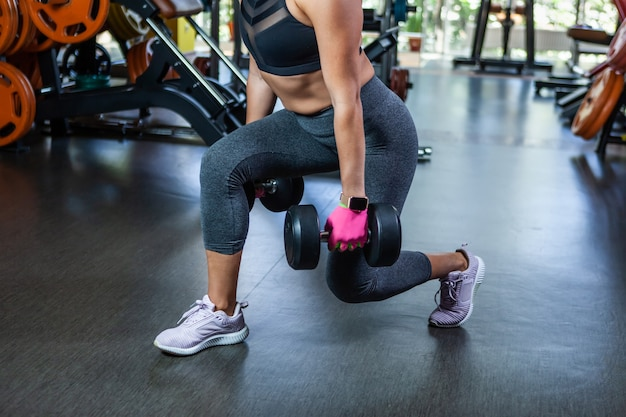 Dopasuj kobieta ćwiczenia z hantlami w dłoniach. hantle rzuca się na siłownię. trening nóg