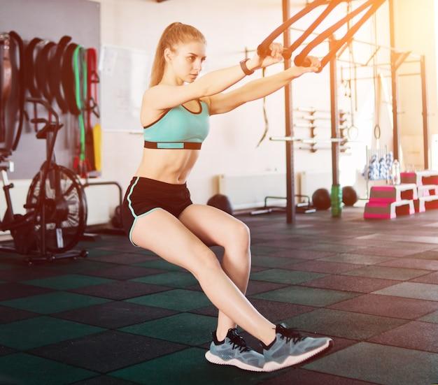 Dopasuj kobieta, ćwiczenia z paskami fitness na siłowni. trening funkcjonalny. sportowy styl życia.