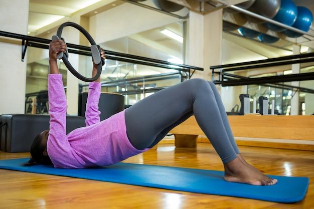 Dopasuj kobieta ćwiczenia z pierścieniem pilates na macie