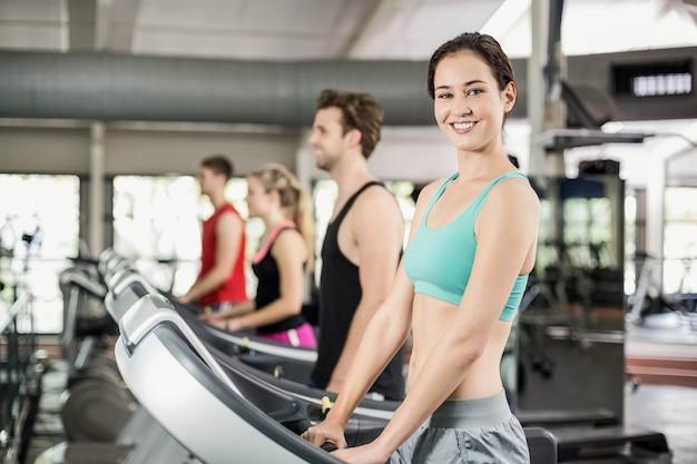 Dopasuj kobieta działa na bieżni na siłowni