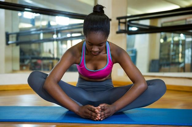 Dopasuj kobieta robi ćwiczenia rozciągające na macie
