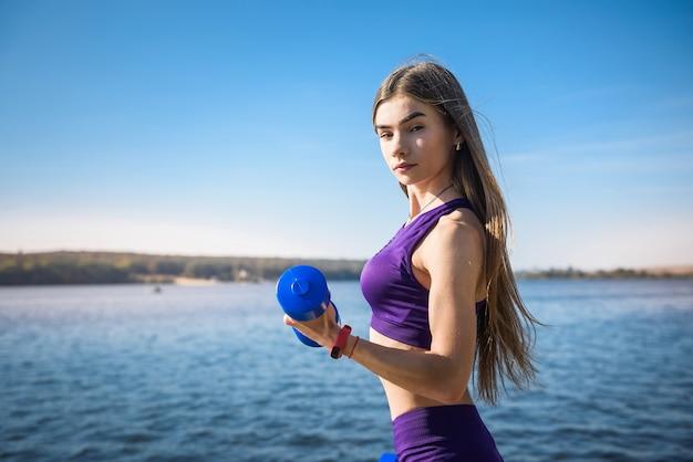 Dopasuj kobieta robi ćwiczenia z hantlami w dłoniach w przyrodzie w pobliżu jeziora