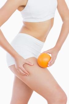 Dopasuj kobieta ściskając tłuszcz na udzie, gdy trzyma pomarańczę
