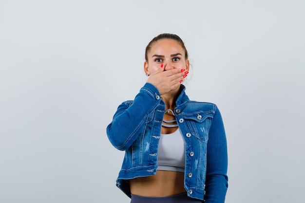 Dopasuj kobieta zakrywając usta ręką w crop top, kurtka dżinsowa, legginsy i patrząc zaskoczony, widok z przodu.