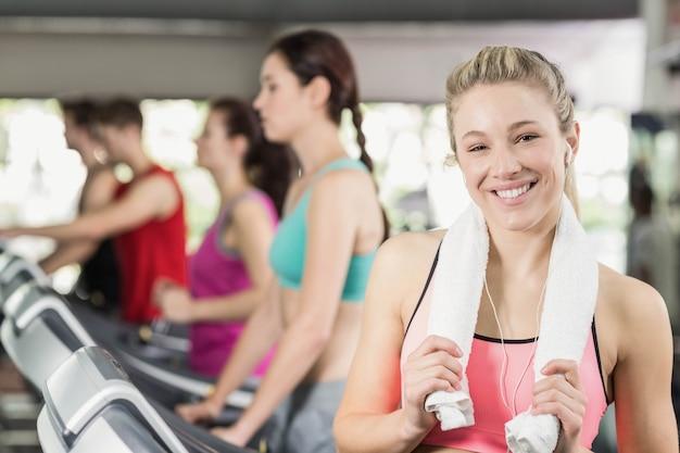 Dopasuj kobietę biegającą na bieżni podczas słuchania muzyki w crossfit