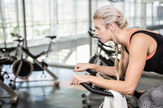 Dopasuj kobietę na rowerze treningowym na siłowni