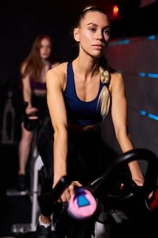 Dopasuj kobietę na siłowni, ćwiczenia na rowerze stacjonarnym w siłowni. ćwiczenia cardio na rowerze, w sportowym stroju, skoncentrowane na treningu