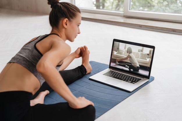 Dopasuj kobietę w odzieży sportowej robi jogę na macie do ćwiczeń w domu za pomocą samouczka oglądania laptopa. trenerka ma wirtualne zajęcia jogi na komputerze