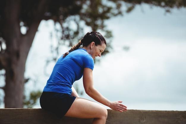 Dopasuj kobiety siedzącej na drewnianej ścianie przeszkody
