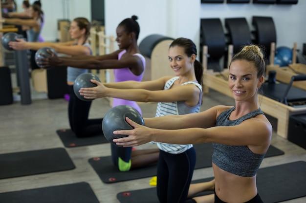 Dopasuj kobiety wykonujące ćwiczenia rozciągające z piłką fitness w siłowni