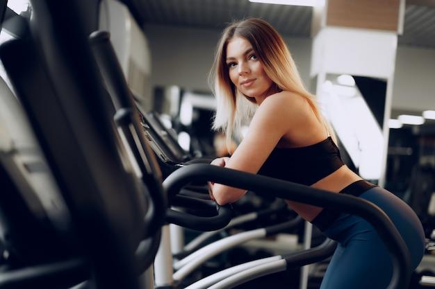 Dopasuj krągła młoda blondynka trenująca w strefie cardio na siłowni