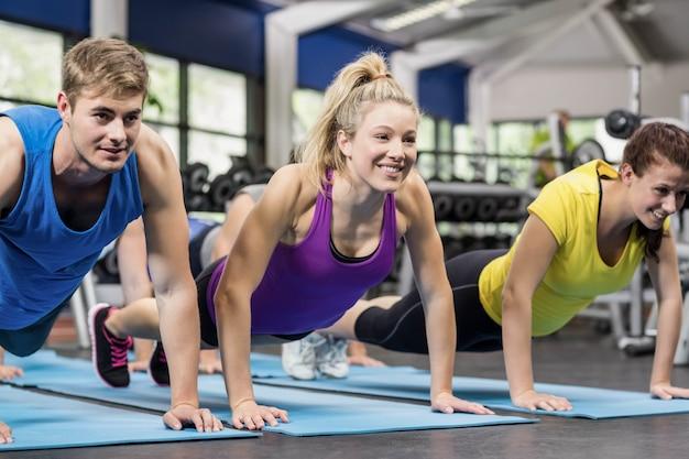 Dopasuj ludzi w pozycji deski na siłowni