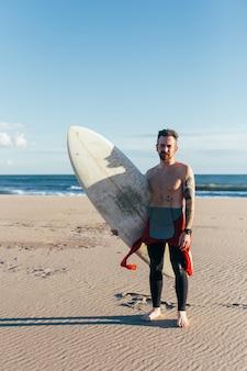 Dopasuj mężczyzna w średnim wieku z deską surfingową na pustej plaży w ciepły letni dzień